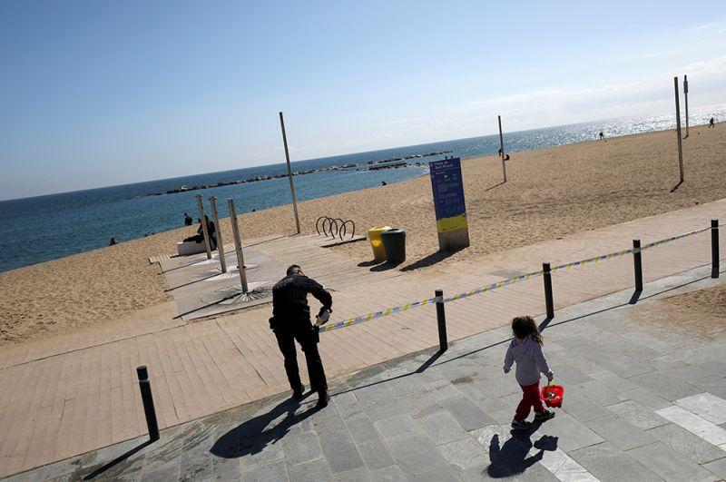 Полицейский закрывает вход на пляж Барселоны.