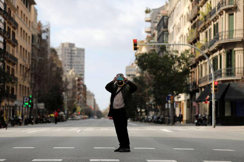 Мужчина в маске  фотографирует пустую улицу Араго в Барселоне.