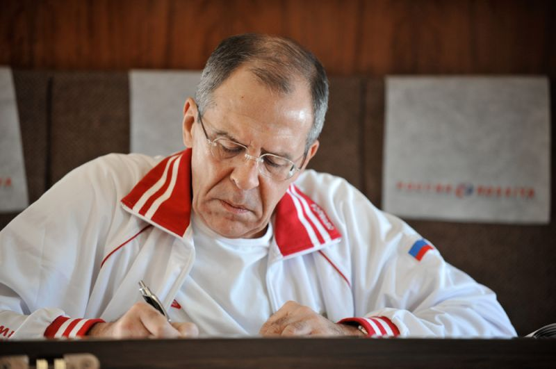 Министр иностранных дел РФ Сергей Лавров в салоне самолета во время работы с документами.