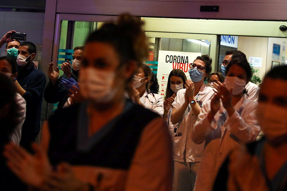 Персонал больницы Fundacion Jimenez Diaz в Мадриде присоединяется к жителям, которые аплодируют им со своих балконов.