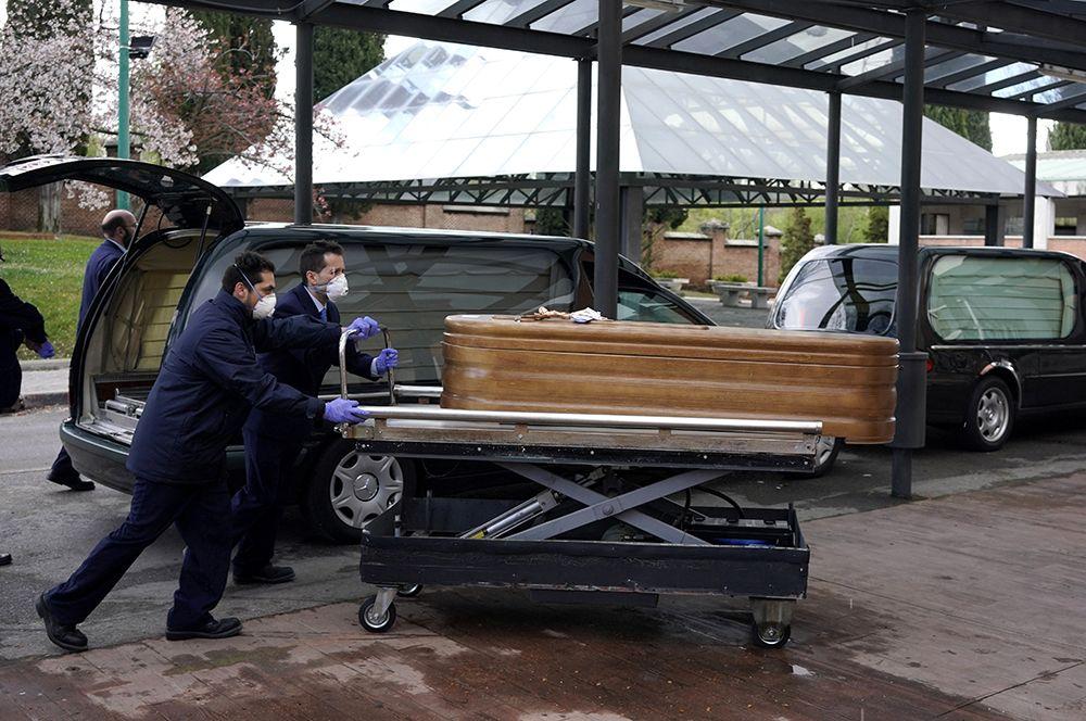 Сотрудники морга входят в крематорий кладбища Ла Альмудена, Мадрид.