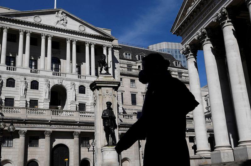 Человек в маске проходит мимо Банка Англии в Лондоне.