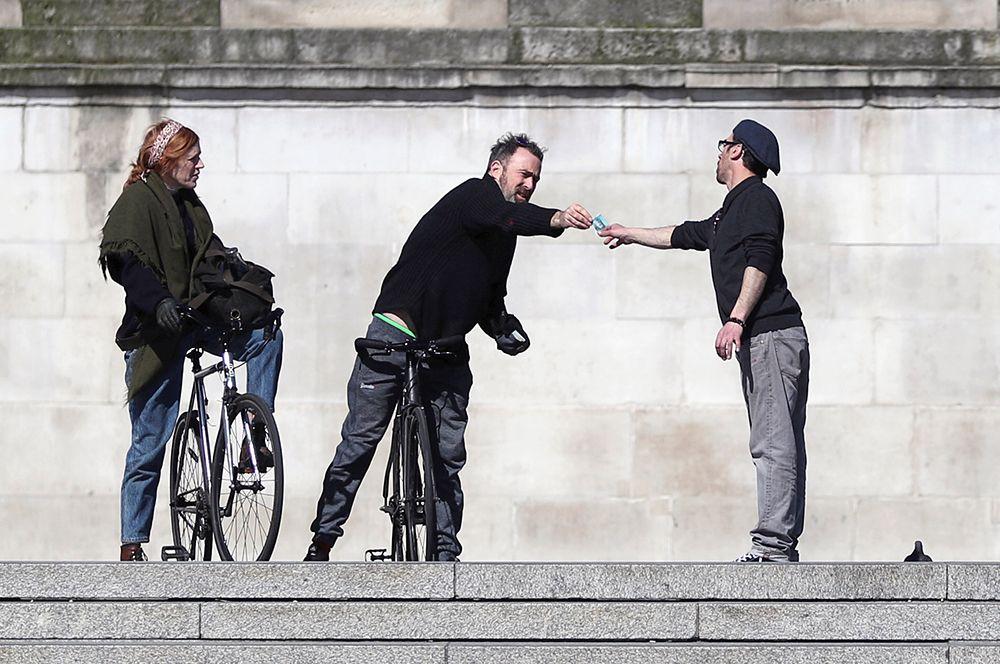 Мужчины держат дистанцию, передавая деньги друг другу, Трафальгарская площадь, Лондон.