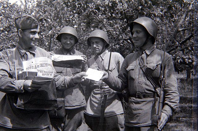 Письмоносец И. Кудояров раздает бойцам письма и газеты.