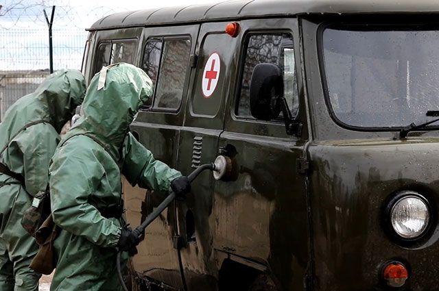 Военнослужащие войск радиационной, химической и биологической защиты проводят обработку поверхностей в ходе проверки готовности войск к возникновению угрозы заражения вирусными инфекциями.