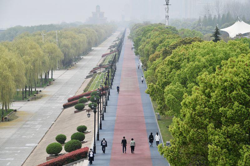 Люди в масках лица гуляют в парке в Ухане.