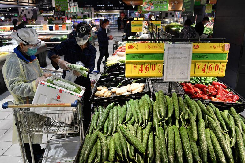 Жители покупают овощи в супермаркете в Ухане.