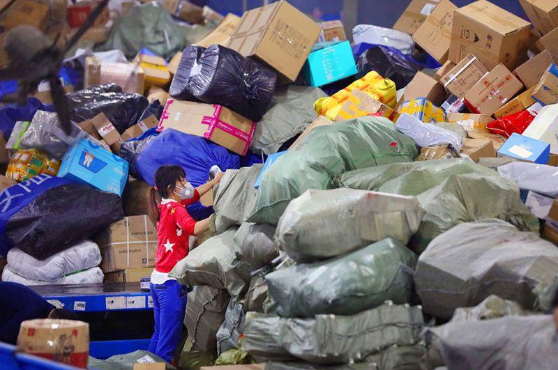Девушка сортирует посылки в логистическом центре в Ухане.
