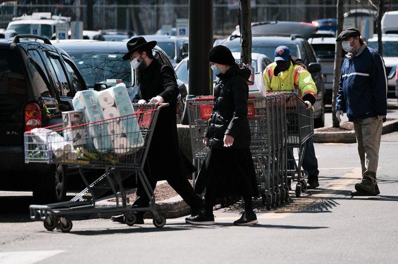 Покупатели в масках на парковке супермаркета Costco.