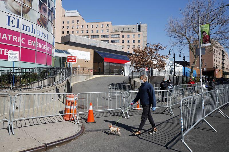 Мужчина выгуливает собаку. На заднем плане - очередь людей, желающих сдать тест на коронавирус.