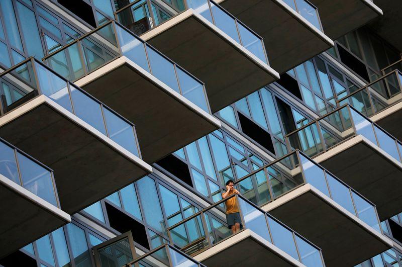 Мужчина на балконе многоквартирного дома в Квинсе. Жителям Нью-Йорка предписывается соблюдать самоизоляцию.