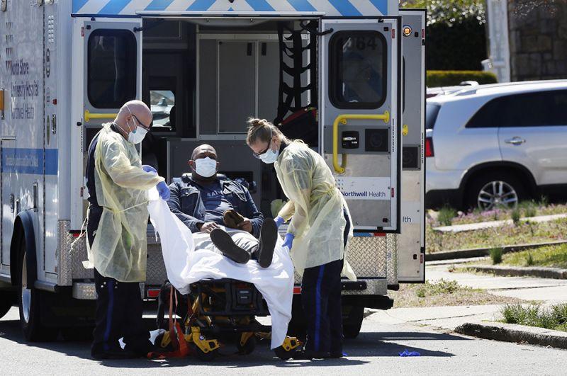 Работники скорой забирают пациента, у которого был обнаружен коронавирус.