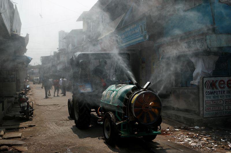 Дезинфекция улиц в районе трущоб в Мумбаи.