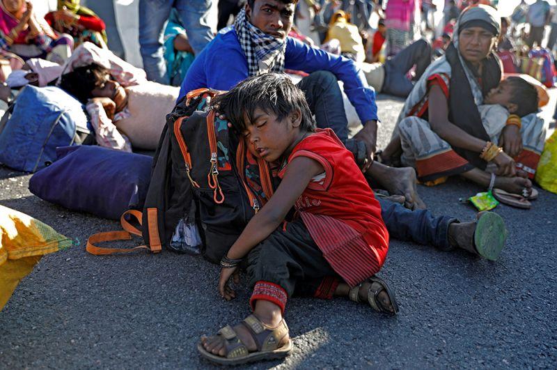 Люди в ожидании транспорта на автобусной станции в Нью-Дели.