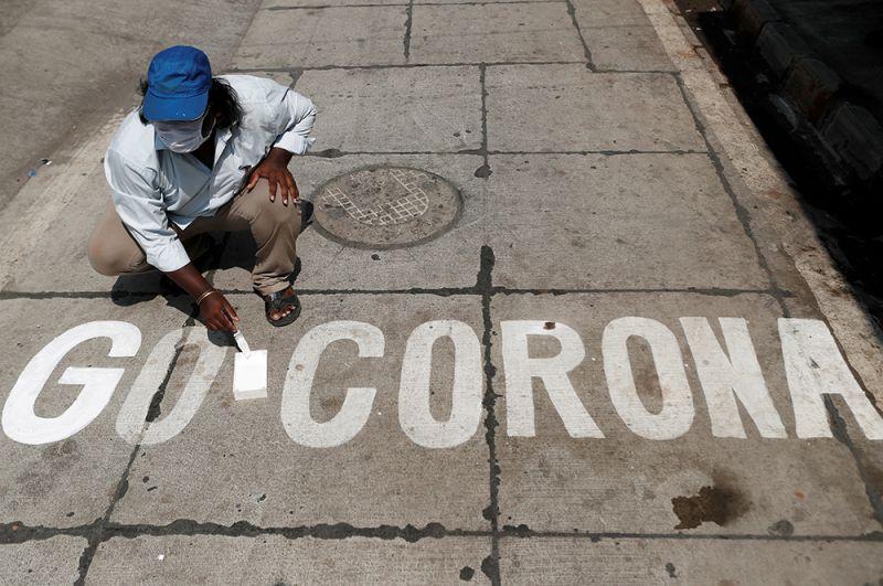 Мужчина делает надпись на асфальте в Мумбаи.