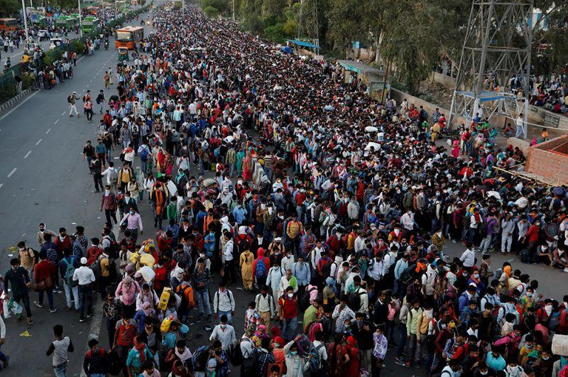 Рабочие на автобусной станции в Нью-Дели ожидают посадки в автобусы, чтобы вернуться домой.