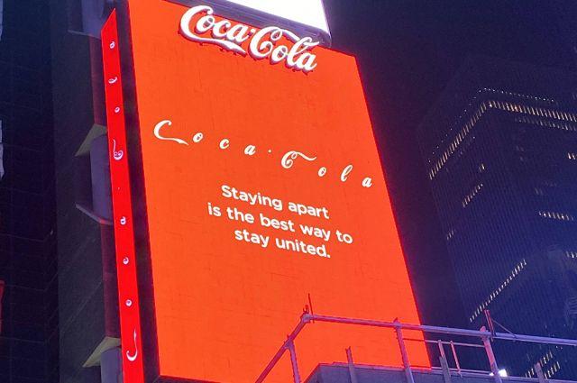 Реклама Coca-Cola, напоминающая о необходимости соблюдать дистанцию, на Таймс-сквер в Нью-Йорке.