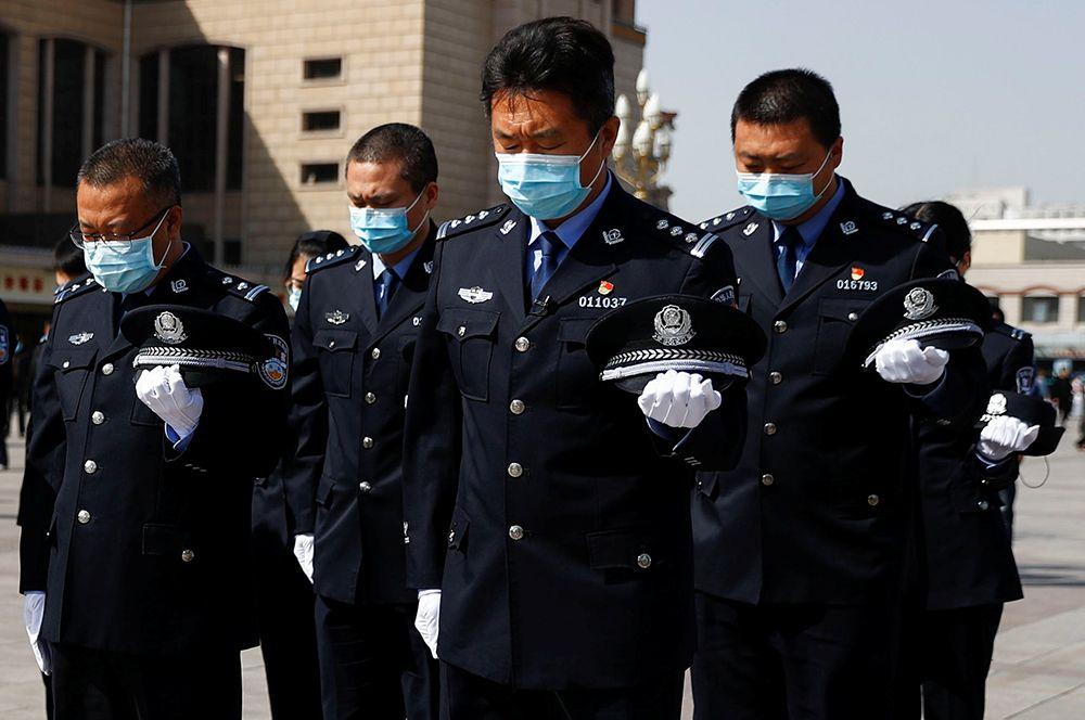 Охранники во время минуты молчания в Пекине.