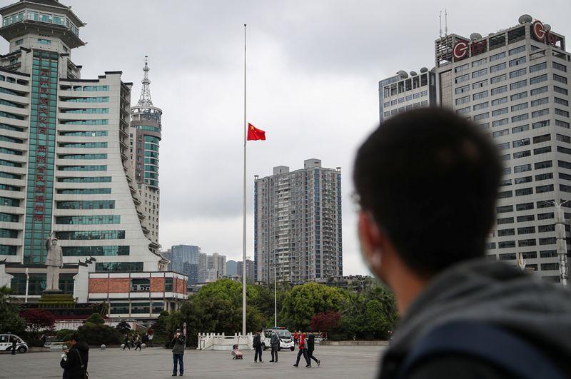Мужчина смотрит на приспущенный национальный флаг в Гуйяне.