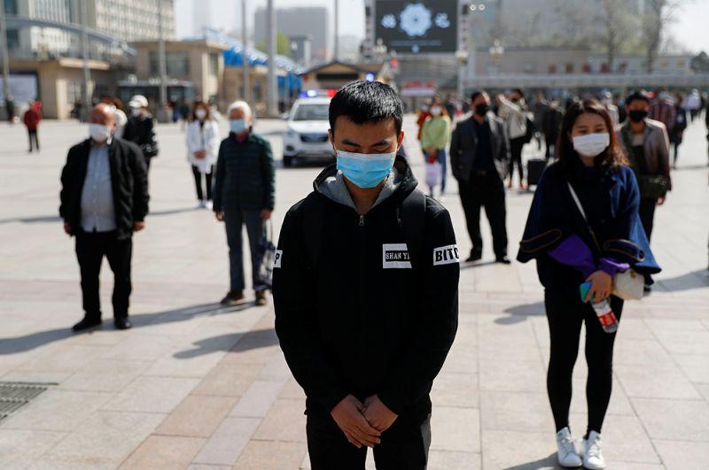 Жители Пекина во время минуты молчания.