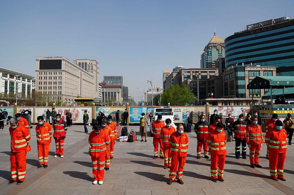Уборщики улиц во время минуты молчания в Пекине.