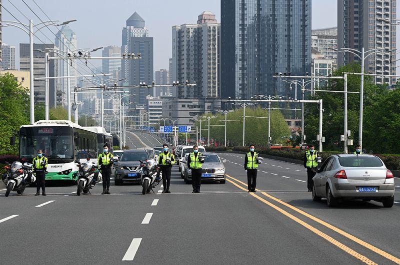 Полицейские и водители автомобилей во время минуты молчания в Ухане.