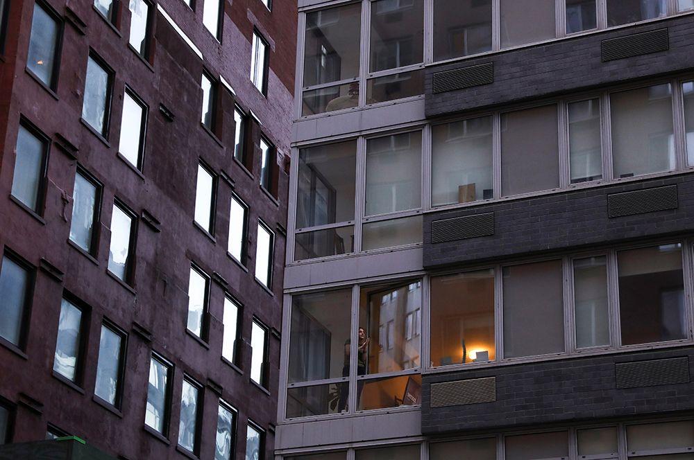 Девушка аплодирует медицинским работникам из окна своей квартиры на Манхэттене.