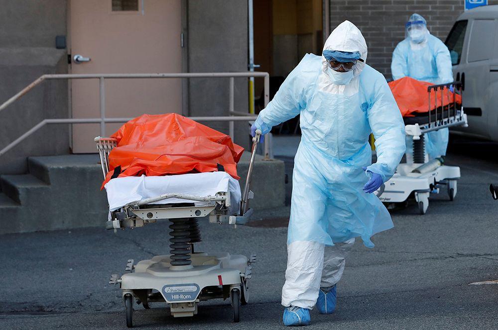 Медицинские работники перевозят тела погибших из центра Wyckoff Heights в Бруклине.