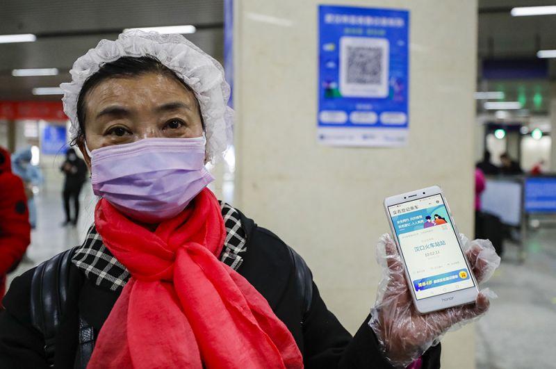 Женщина показывает экран своего мобильного телефона с открытой программой для сканирования QR-кода на станции метро в Ухане.