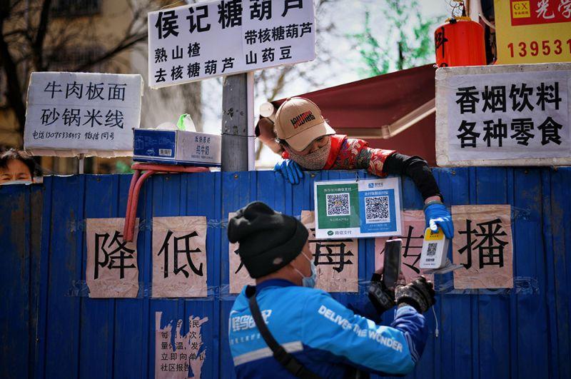 Сотрудник службы доставки сканирует свой QR-код у работника ресторана перед тем, как забрать у него еду, Цзинань.