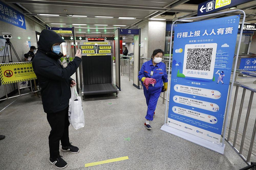 Пассажир сканирует QR-код перед входом в метро в Ухане.