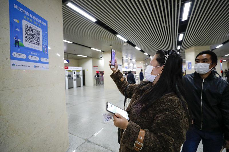 Пассажиры сканируют QR-коды перед тем, как сесть на поезд метро в Ухане.