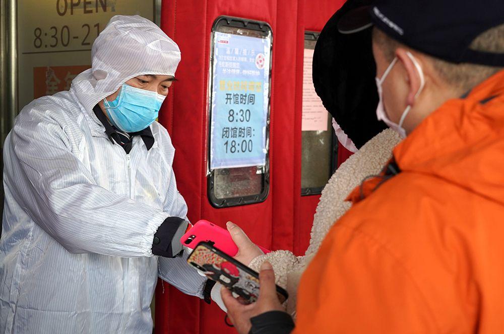 Сотрудник сканирует QR-коды жителей у входа в супермаркет в Чжэнчжоу.
