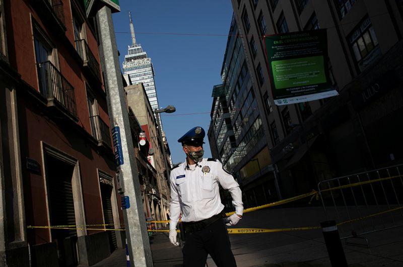 Полицейский охраняет главную улицу в центре Мехико, Мексика.