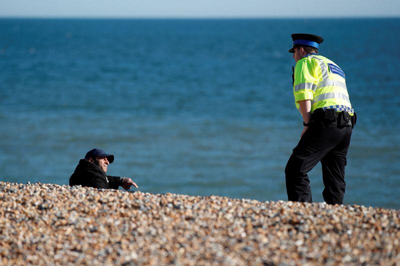 Полицейский убеждает мужчину уйти с пляжа в Брайтоне, Великобритания.