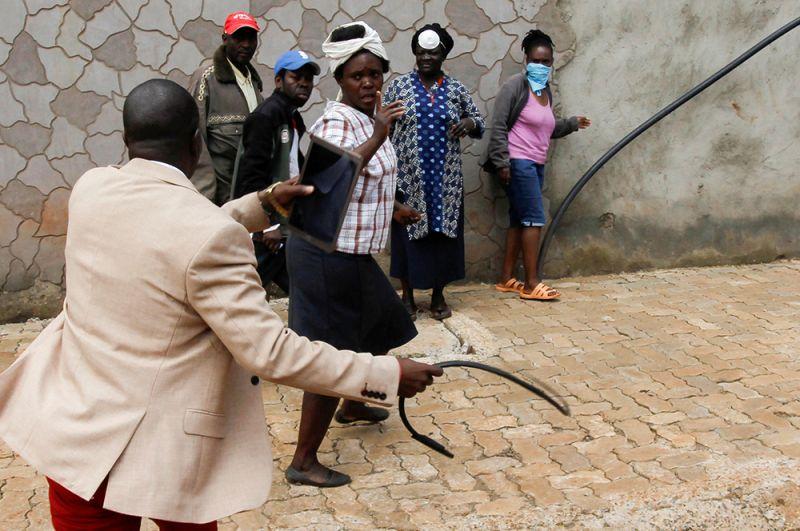 Чиновник использует кнут, чтобы разогнать жителей, собравшихся для получения продовольственных пайков, Найроби, Кения.