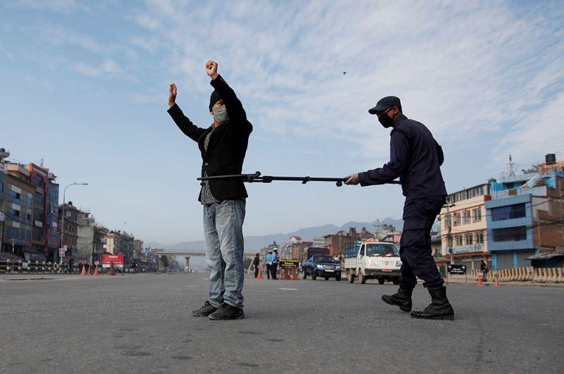 Полицейский задерживает мужчину, нарушившего режим, в Катманду, Непал.