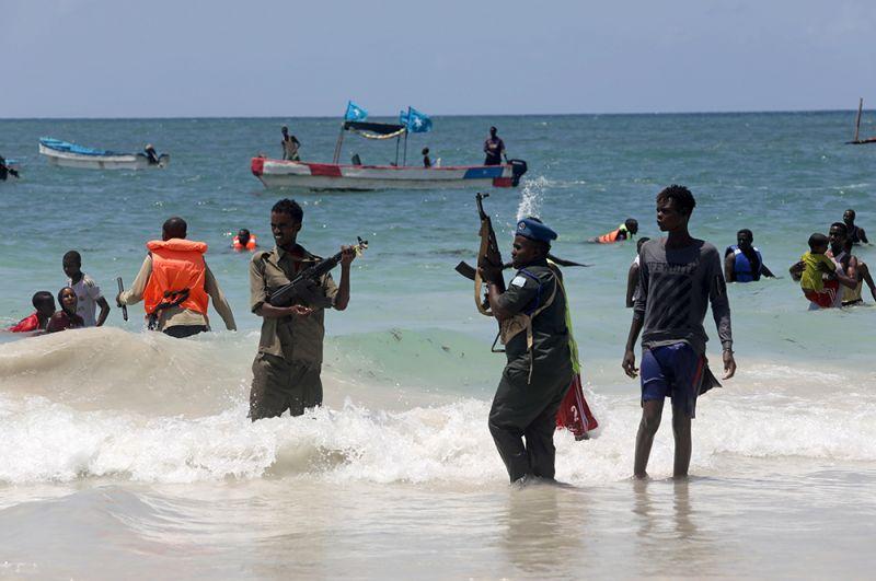 Полицейский пытается разогнать купающихся на пляже Лидо в Могадишо, Сомали.
