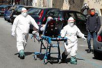 Медперсонал вполном защитном снаряжении перевозит пациента сподозрением накоронавирус поулице Неаполя. Транспортировка намашинах вИталии работает изрук вон плохо.