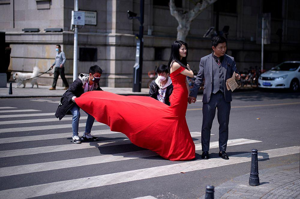 Молодожены во время свадебной фотосессии на улицах города.