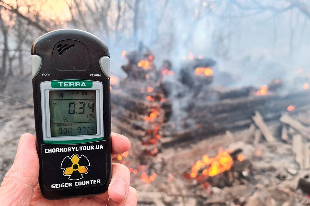 Счетчик Гейгера измеряет уровень радиации на месте пожара неподалеку от села Раговка.