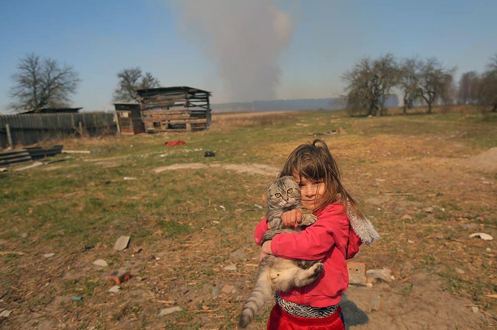 Девочка с котом во дворе частного дома в селе Раговка.