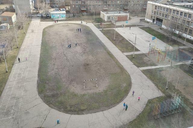 Возле школы в Магнитогорске в период самоизоляции гуляет много детей.