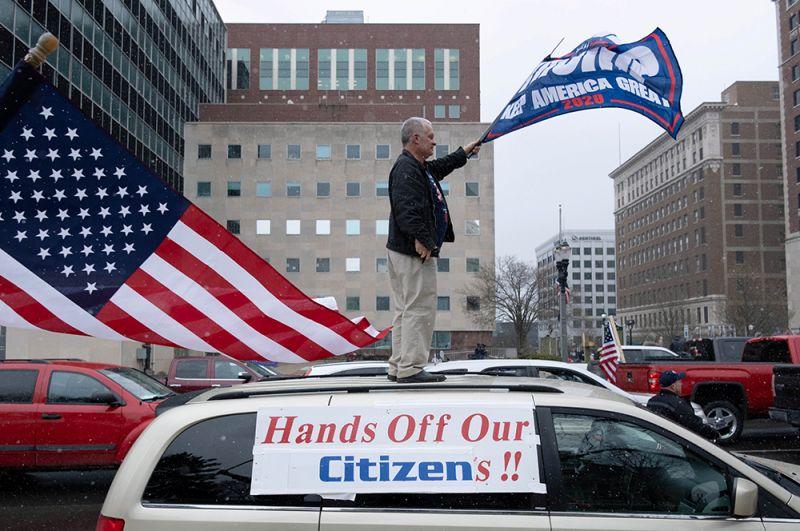 Лансинг, Мичиган. Надпись на плакате: «Руки прочь от наших граждан».