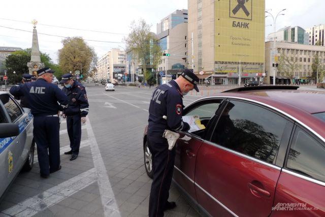 Сотрудники ДПС проверяют водительские пропуска на центральной улице Краснодара.