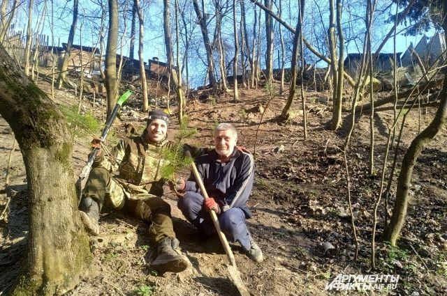Роман Бут-Гусаим и Александр Карпов сажают сосны на только что очищенном от мусора склоне оврага около своих домов.