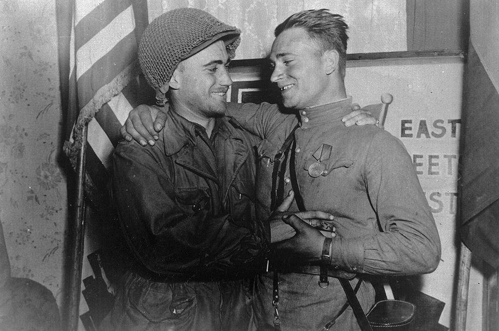 Лейтенант Робертсон и лейтенант Сильвашко на фоне надписи «Восток встречается с Западом», символизирующей историческую встречу союзников на Эльбе.