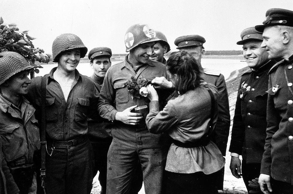 Советская медсестра Любовь Казиченко дарит цветы американскому солдату Карлу Робинсону.