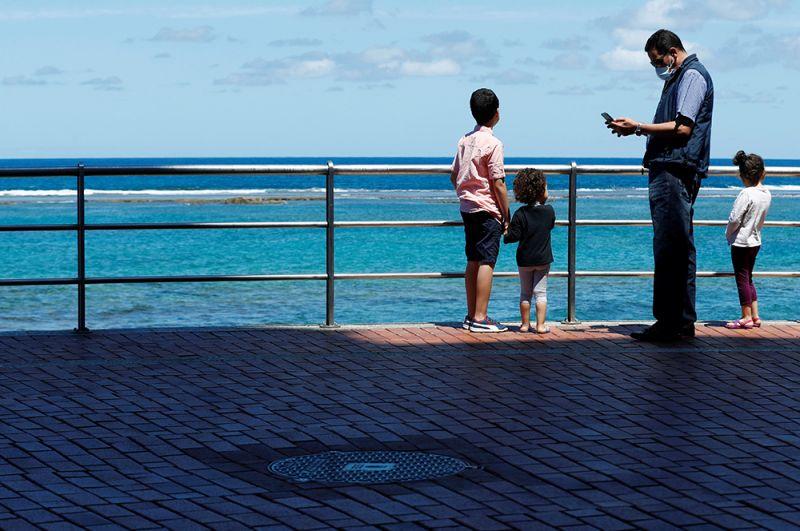 Семья во время прогулки на набережной острова Гран-Канария, Испания.