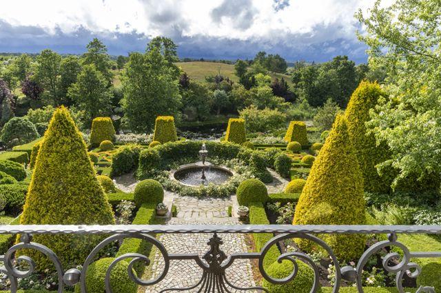 Фонтан органично окружает зелёная архитектура израстений.